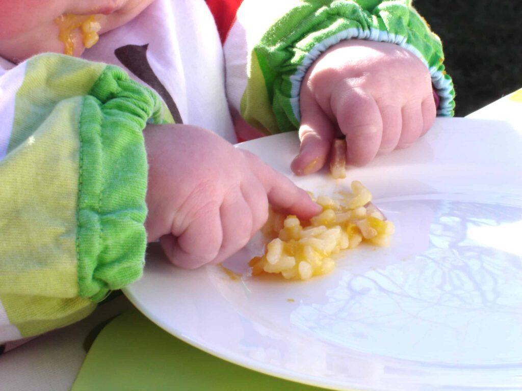 Bambina che si svezza da sola prendendo i chicchi di riso con le dita