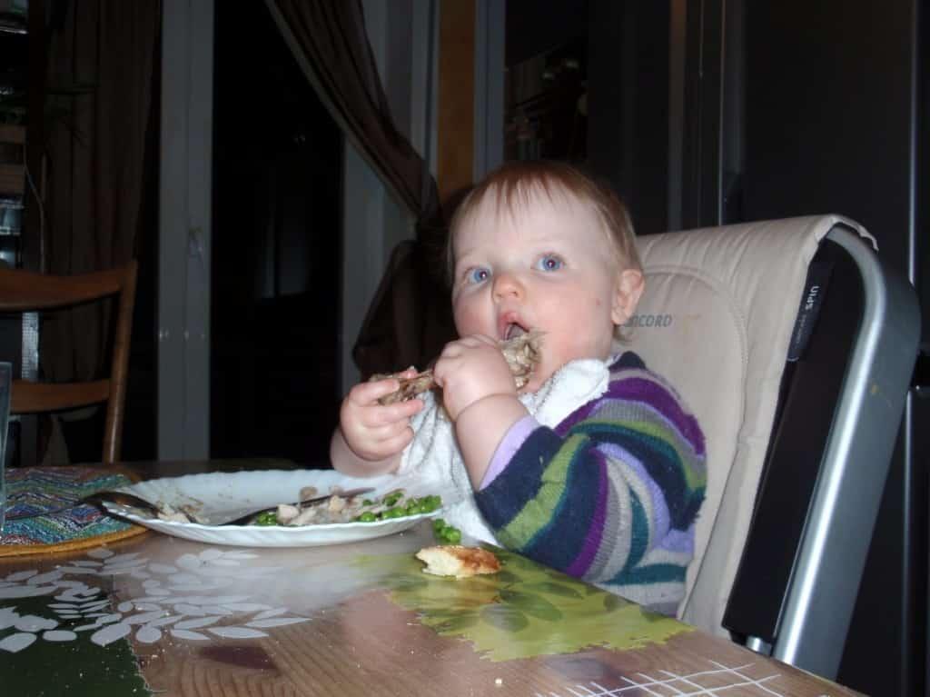 Bambina si svezza da solo con il pollo