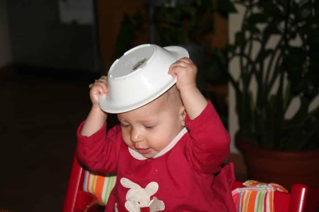 Bambina che fa autosvezzamento con piatto in testa