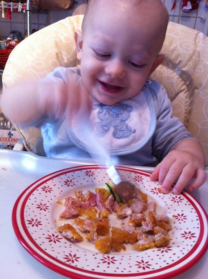 Bambino procede a svezzarsi da solo mangiando da un piatto
