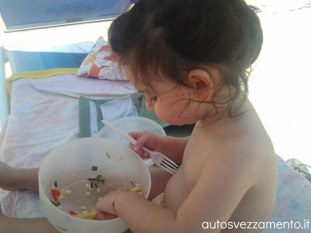 Bambina si svezza da sola in spiaggia mangiando un bel piatto di pasta