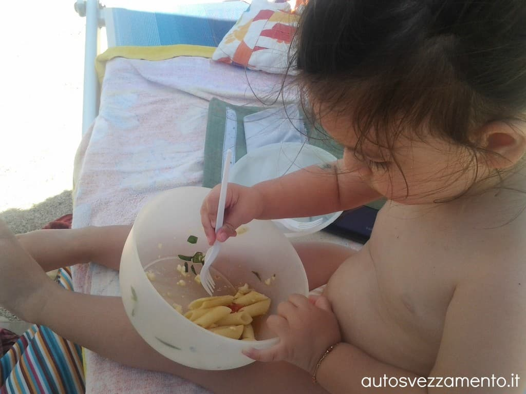 Bambina fa autosvezzamento in spiaggia